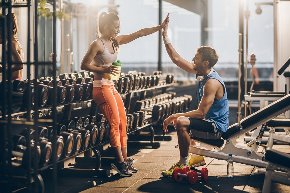 Happy athletic couple giving each other high five after finishing sports training in a gym.