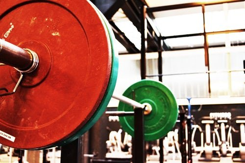 red-and-green-weights-on-barbell-in-empty-gym