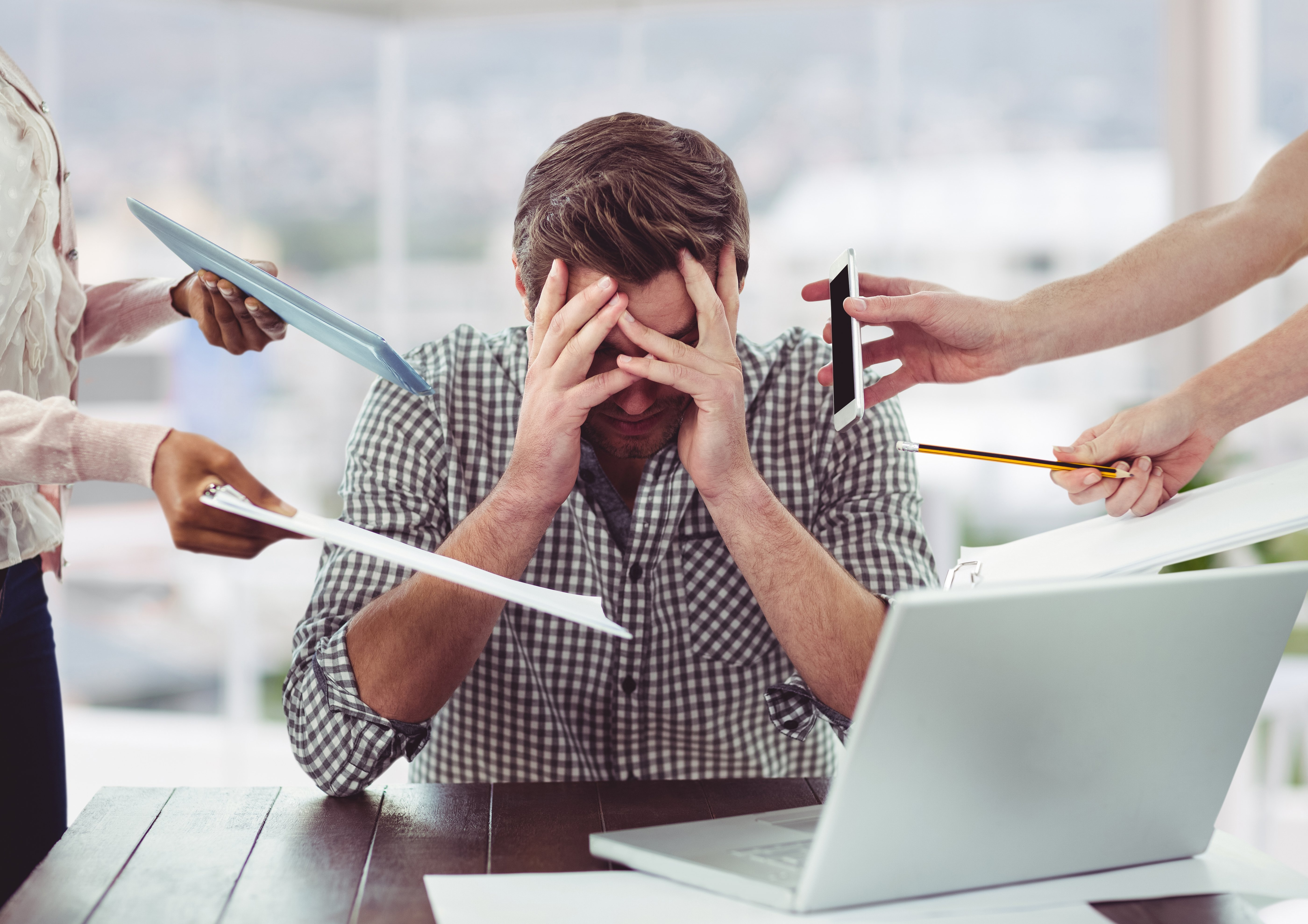 Stressed man frustrated with electronic devices in office