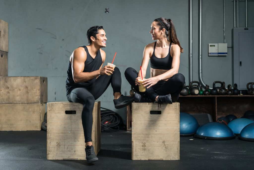 two fitness junkies drinking a smoothie as smart food choices after a workout