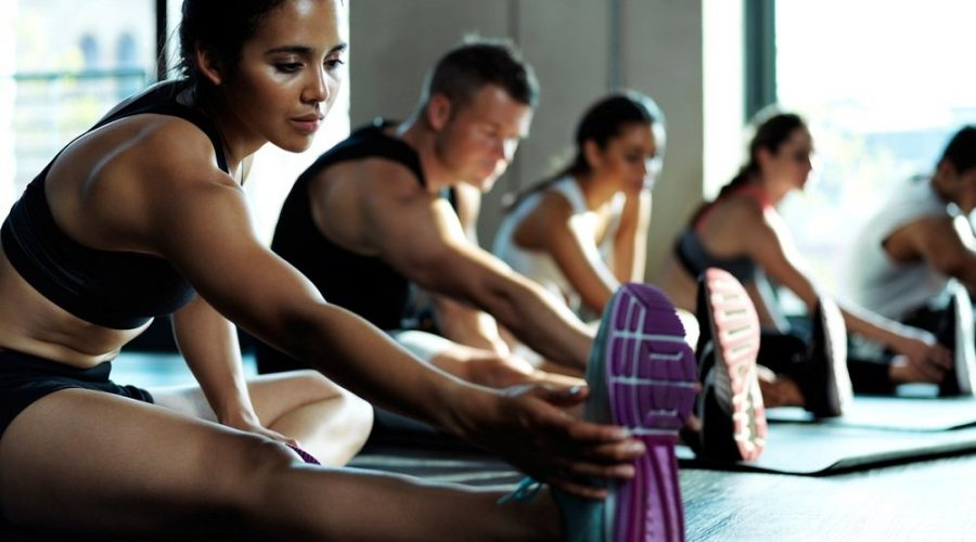 Shot f a group of young fit people stretching before a workout session inside of  a studio