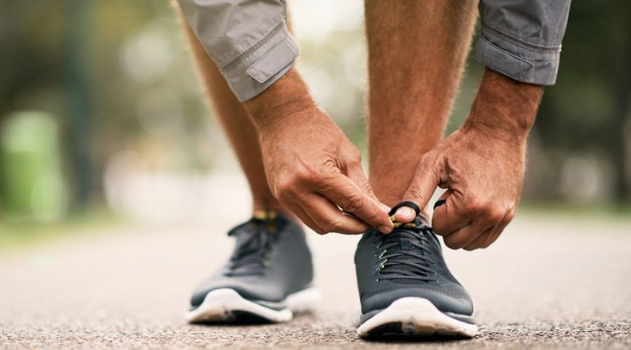 Cropped shot of a man tying his shoelaces while out for a run in the park