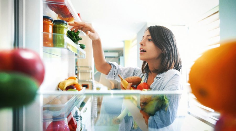 woman-picking-out-healthy-foods-from-her-refrigerator