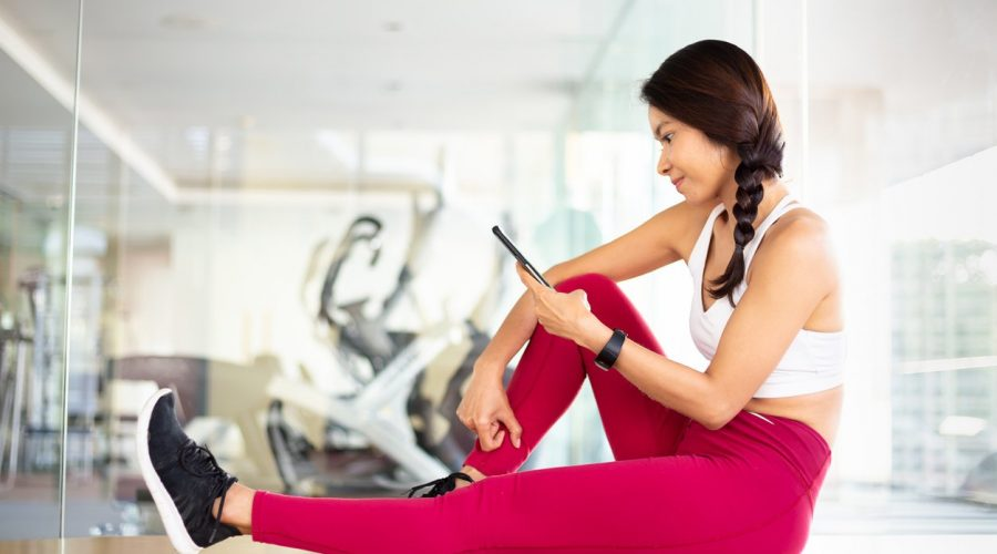 Young female athletic fitness people using a smart phone inside gym - health technology and fitness app concept.