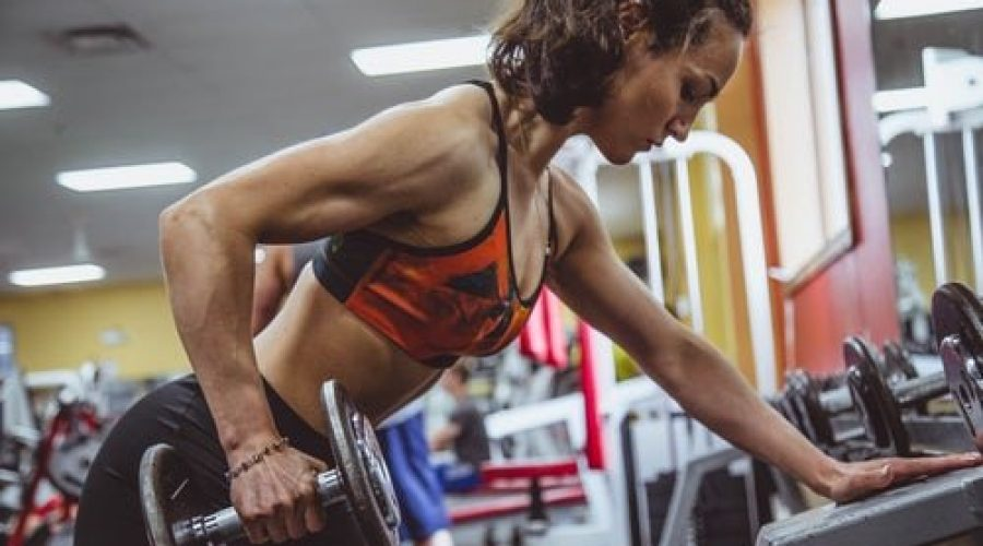 woman-with-brown-hair-in-ponytail-lifting-weights-targeting-triceps-and-shoulders