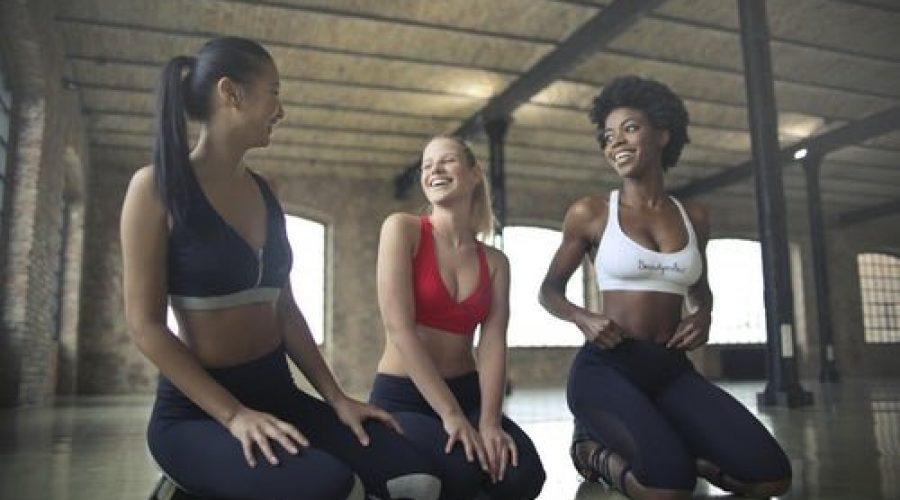 three-female-friends-in-sports-bras-and-leggings-kneeling-on-gym-floor-resting-between-workout-exercises